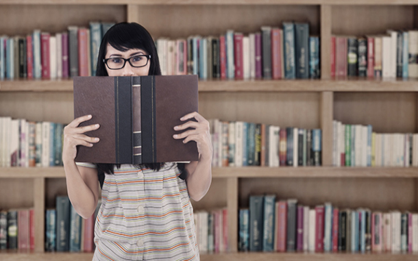 Asian female student reading book at library